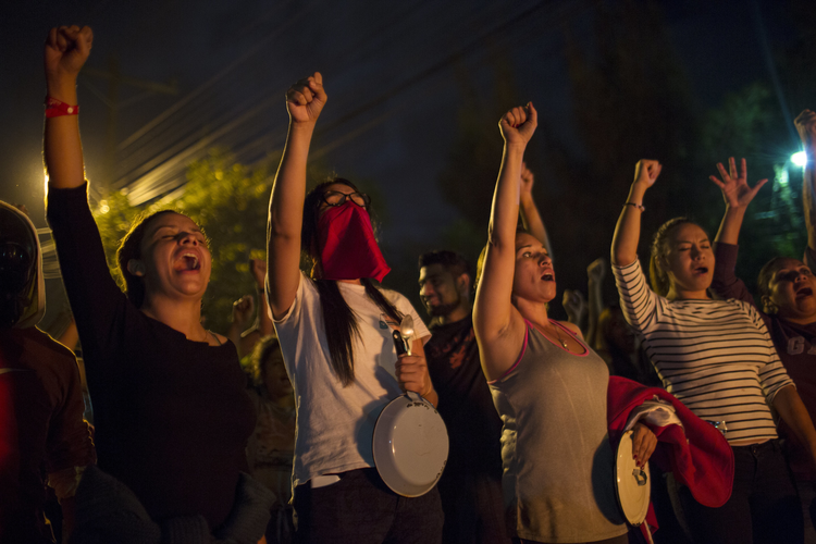 Anti-government protestors shout slogans during a government imposed dawn-to-dusk curfew in Tegucigalpa, Honduras, on Dec. 3. (AP Photo/Rodrigo Abd)