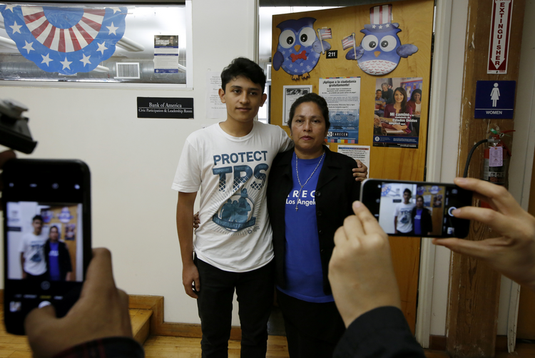 U.S. citizen Benjamin Zepeda, 14, with his mother Lorena Zepeda, who benefits from Temporary Protected Status, have their photo taken after a news conference in Los Angeles on Jan. 8. (AP Photo/Damian Dovarganes)