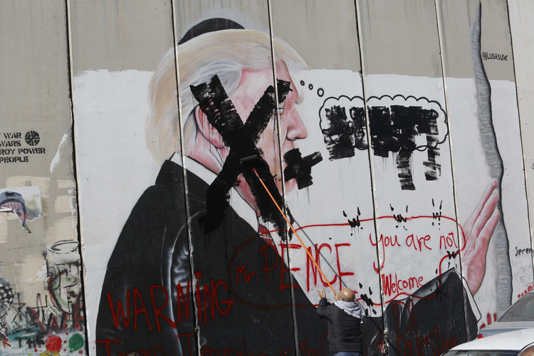 In this Dec. 7, 2017 file photo, a Palestinian defaces a painting on the separation barrier of U.S. President Donald Trump, with a warning that Vice President Mike Pence is not welcome, in Bethlehem, West Bank. Palestinian Christians say Pence's brand of evangelical Christianity, with its fervent embrace of modern-day Israel as fulfilment of biblical prophecy, lacks their faith's compassion and justice, including for those who have endured half a century of Israeli occupation. (AP Photo/Nasser Shiyoukhi, Fi