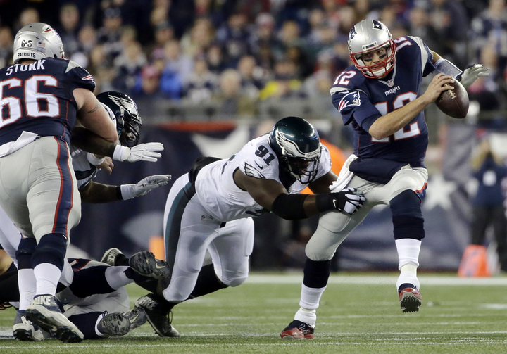 In this Dec. 6, 2015 photo, New England Patriots quarterback Tom Brady (12) scrambles away from Philadelphia Eagles defensive end Fletcher Cox (91) during a game in Foxborough, Mass. (AP Photo/Steven Senne, File).