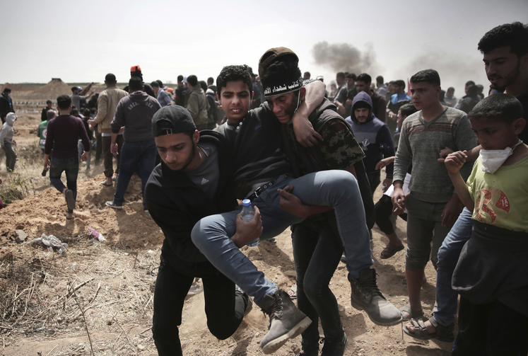 Palestinian protesters evacuate a wounded youth who was shot by Israeli troops during a protest at the Gaza Strip's border with Israel on April 13. Palestinians streamed to tent camps on Gaza's border with Israel for a third mass protest. (AP Photo/ Khalil Hamra)
