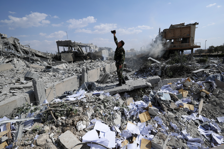 A Syrian soldier documents the damage to the Syrian Scientific Research Center from U.S., British and French military strikes on April 14. (AP Photo/Hassan Ammar)