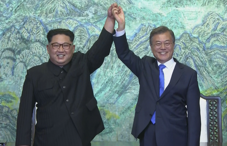 In this image made from video provided by Korea Broadcasting System (KBS), North Korean leader Kim Jong Un, left, and South Korean President Moon Jae-in raise their hands after signing on a joint statement at the border village of Panmunjom in the Demilitarized Zone Friday, April 27, 2018. (Korea Broadcasting System via AP)