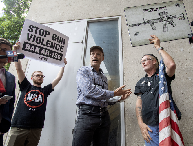 National Rifle Association member Jim Whelan, center, talks with protester David Lyles, right, outside the NRA Annual Meeting on May 4 in Dallas. (AP Photo/Jeffrey McWhorter)