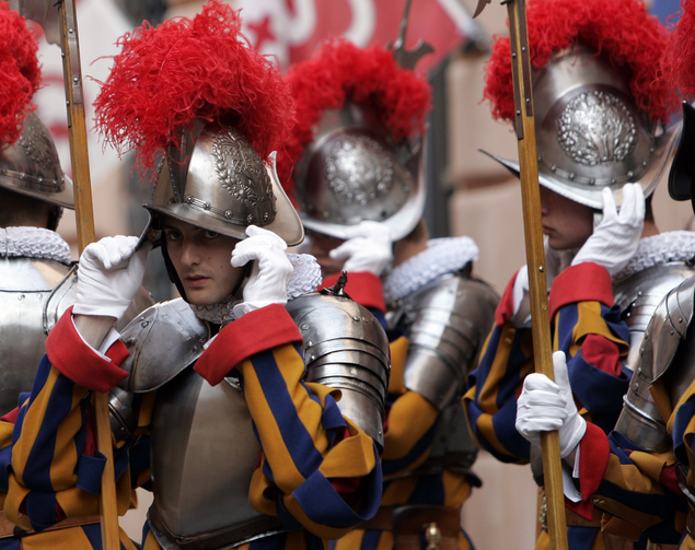 In this May 6, 2008 file photo, new Vatican Swiss Guards adjust their helmets prior to a swearing-in ceremony at the Vatican. The world's oldest standing army is getting some new headgear. The Swiss Guards plan to replace their metal helmets with plastic PVC ones made with a 3-D printer, giving the pope's army cooler and more comfortable headgear when standing guard for hours at a time. (AP Photo/Alessandra Tarantino, pool)