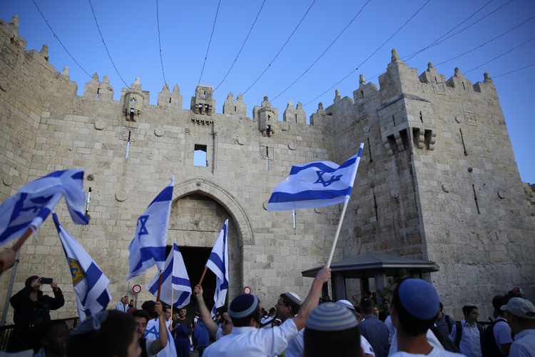 Israelis wave national flags outside the Old City's Damascus Gate, in Jerusalem, Sunday, May 13, 2018. Israel is marking the 51st anniversary of its capture of east Jerusalem in the 1967 Middle East war. (AP Photo/Ariel Schalit)