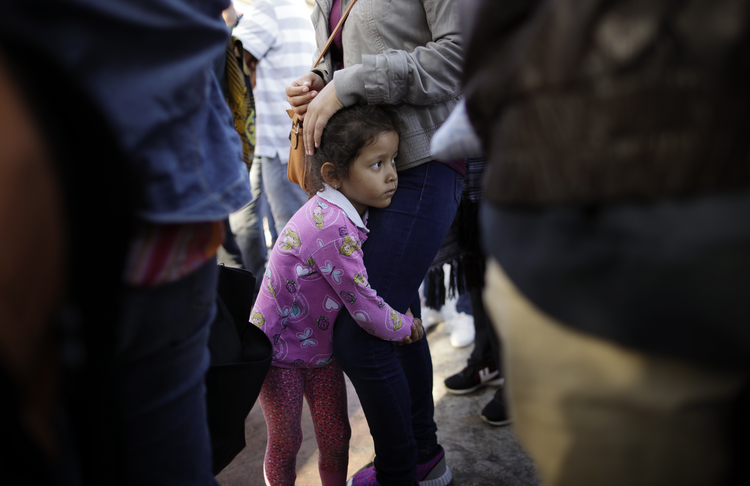 Nicole Hernandez, of the Mexican state of Guerrero, holds on to her mother as they wait with other families in Tijuana, Mexico, on June 13 to request political asylum in the United States. (AP Photo/Gregory Bull, file)