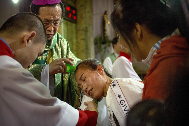 Chinese Bishop Joseph Li Shan baptizes a woman during a Mass at the Cathedral of the Immaculate Conception, a government-sanctioned Catholic church in Beijing, on Sept. 22. (AP Photo/Mark Schiefelbein, File)