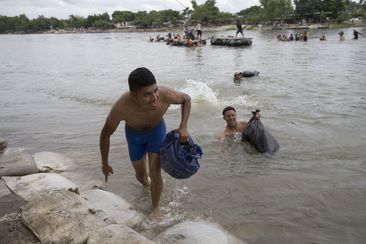 Central American migrants reach the shore on the Mexican side of the Suchiate River after wading across from Guatemala on Oct. 20. Thousands of migrants from El Salvador, Honduras and Guatemala are making their way north through Mexico. (AP Photo/Moises Castillo)
