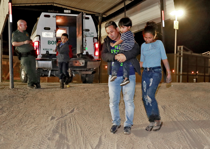 "A Honduran man carries his 3-year-old son as his daughter and other son follow to a transport vehicle after being detained by U.S. Customs and Border Patrol agents in San Luis, Ariz., on July 18. Federal judges in California have challenged more of the Trump administration's ""zero-tolerance"" policy on illegal immigration. (AP Photo/Matt York, File)"
