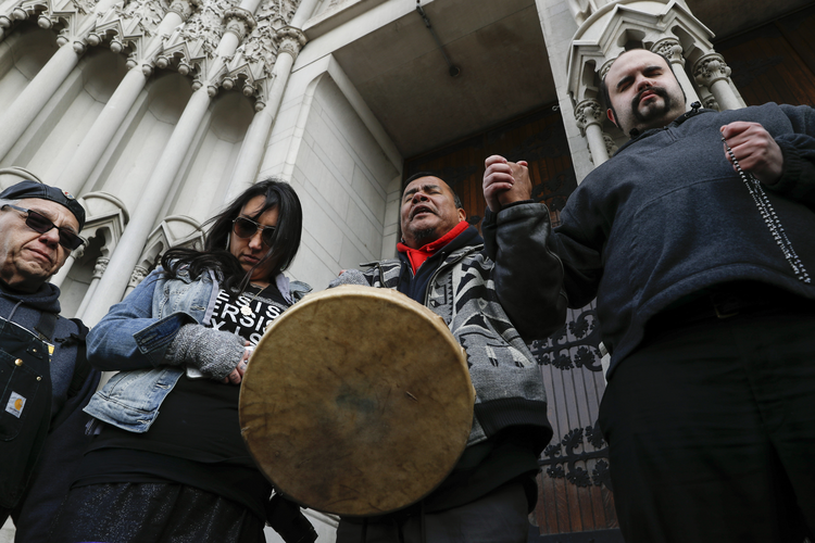 Native American protestors hold hands with parishioner Nathanial Hall, right, during a group prayer outside the Catholic Diocese of Covington onJan. 22, 2019, in Covington, Ky.(AP Photo/John Minchillo)