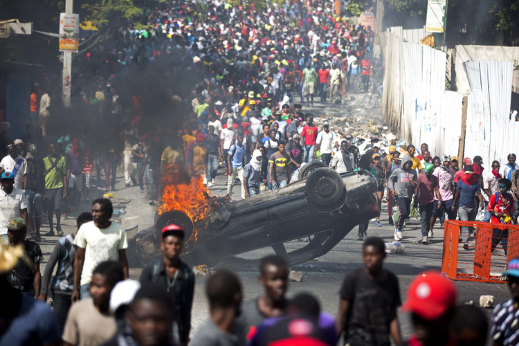 An overturned car burns during a protest demanding the resignation of Haitian President Jovenel Moise in Port-au-Prince, Haiti, on Feb. 12. (AP Photo/Dieu Nalio Chery)