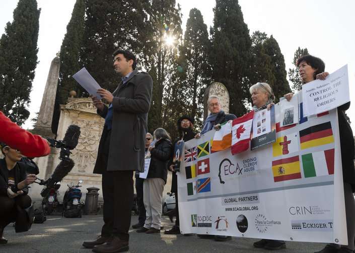Child psychologist and founding member of the Ending Clergy Abuse (ECA) organization, Miguel Hurtado from Spain, center, reads an open letter to the Benedictine order outside the St. Anselm on the Aventine Benedictine complex in Rome on Feb. 22. (AP Photo/Domenico Stinellis)