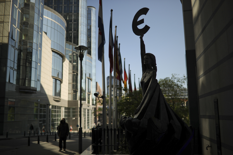 People walk past a sculpture with the Euro currency logo outside the European Parliament building in Brussels on May 15, 2019. Europeans from 28 countries will head to the polls May 23-26 to choose lawmakers to represent them at the European Parliament for the next five years. (AP Photo/Francisco Seco)