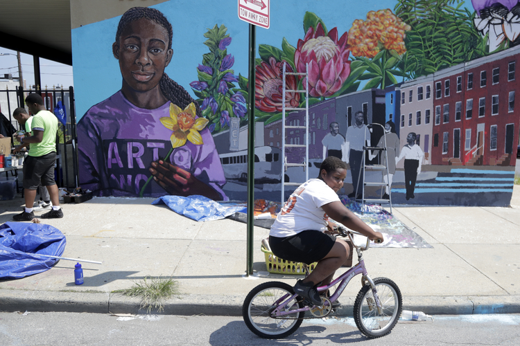 "A boy rides his bicycle on July 29 after volunteering to paint a mural outside the New Song Community Church in the Sandtown section of Baltimore. In the latest rhetorical shot at lawmakers of color, President Donald Trump over the weekend vilified Rep. Elijah Cummings majority-black Baltimore district as a ""disgusting, rat and rodent infested mess"" where ""no human being would want to live."" (AP Photo/Julio Cortez)"