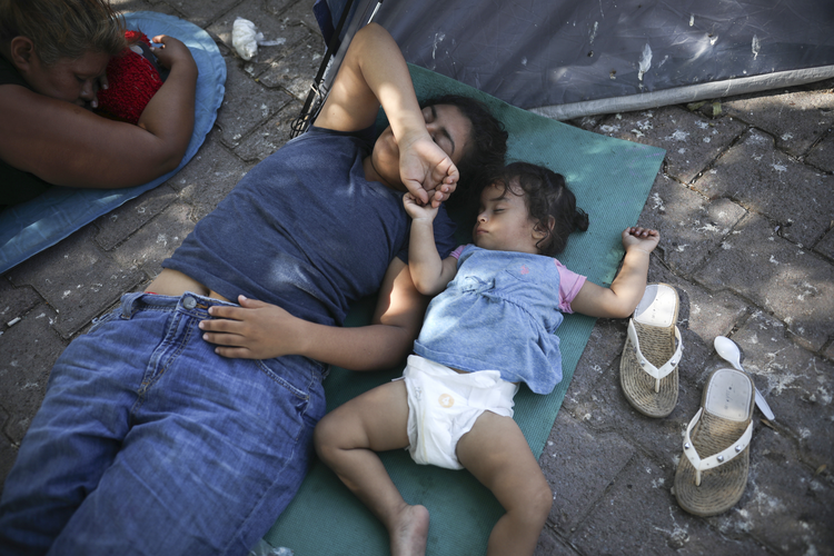 Migrants rest near a Mexican immigration center where migrants set up camp in Matamoros, Mexico, on Aug. 1. Turning Mexican border cities into waiting rooms for asylum seekers may be the Trump administration's most forceful response yet to a surge of migrants, many of them Central American families. (AP Photo/Emilio Espejel)