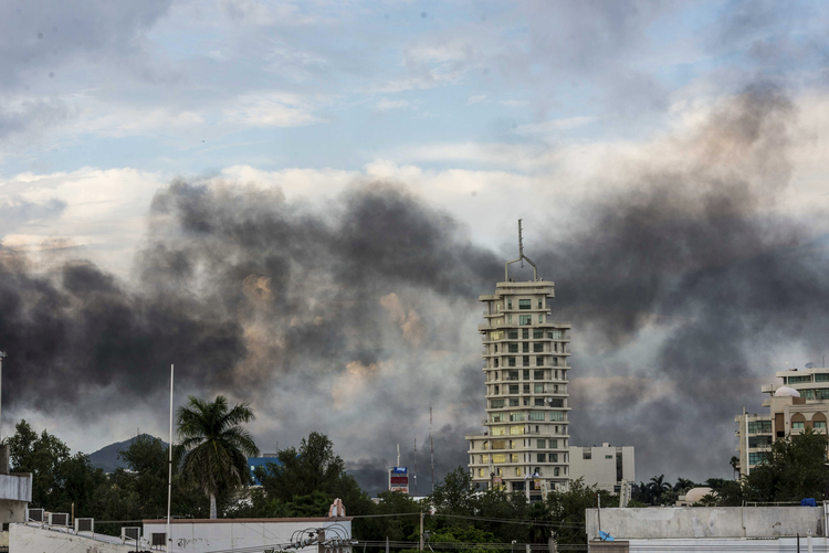 Clouds of smoke from burning cars mar the skyline of Culiacan, Mexico. The Mexican city lived under drug cartel terror for 12 hours as gang members forced the government to free a drug lord. (AP Photo/Hector Parra)