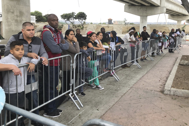 Asylum seekers in Tijuana, Mexico, listen to names being called from a waiting list at a border crossing in San Diego on Sept. 26. (AP Photo/Elliot Spagat,File)