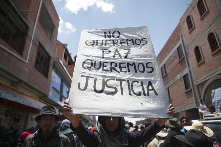 "A supporter of former President Evo Morales holds a sign with a handwritten message that reads in Spanish: ""We don't want peace, We want justice,"" during a protest at a blocked highway in El Alto, on the outskirts of La Paz, Bolivia, Wednesday, Nov. 20, 2019. (AP Photo/Natacha Pisarenko)"