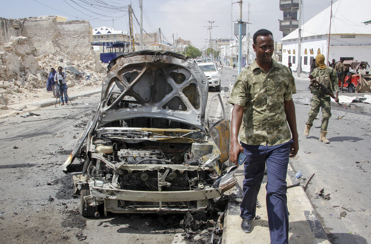 Security forces and others walk past the wreckage of vehicles after a vehicle bomb attack on a security checkpoint located near the presidential palace, in Mogadishu, Somalia, Wednesday, Jan. 8, 2020. (AP Photo/Farah Abdi Warsameh)