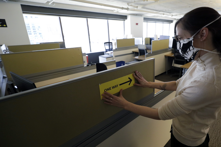 Stephanie Jones posts a sign mandating one-way foot traffic among the cubicles at the design firm Bergmeyer, in Boston, in response to the coronavirus pandemic. (AP Photo/Steven Senne)