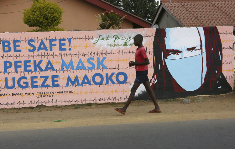 A young boy walks past a wall with graffiti urging people to wear face masks in Harare, on May28. Manhunts have begun after hundreds of people fled quarantine centres in Zimbabwe and Malawi. Authorities worry they will spread COVID-19 in countries whose health systems can be rapidly overwhelmed. (AP Photo/Tsvangirayi Mukwazhi)