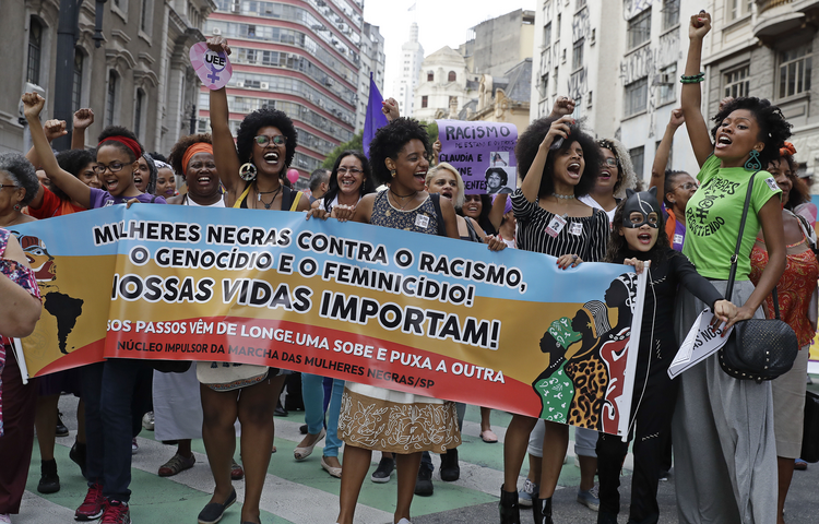 "Activists march holding a banner that reads in Portuguese ""Black women against racism, genocide and femicide. Our lives matter,"" during a demonstration to mark International Women's Day, in Sao Paulo, Brazil, on March 8, 2017. (AP Photo/Andre Penner)"