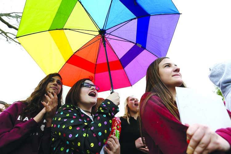 Saffron Edwards, 15, holds up a rainbow-colored umbrella during a student walkout at Dowling Catholic High School in Des Moines, Iowa. Students, alumni and supporters were protesting the school's decision not to hire a gay teacher in April 2015. (AP Photo/The Des Moines Register, Michael Zamora)
