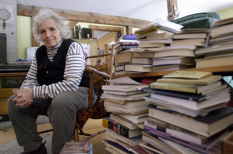 Grace Paley sits beside a pile of books in her home in Thetford Hill, Vt., April 9, 2003 (AP Photo/Toby Talbot).