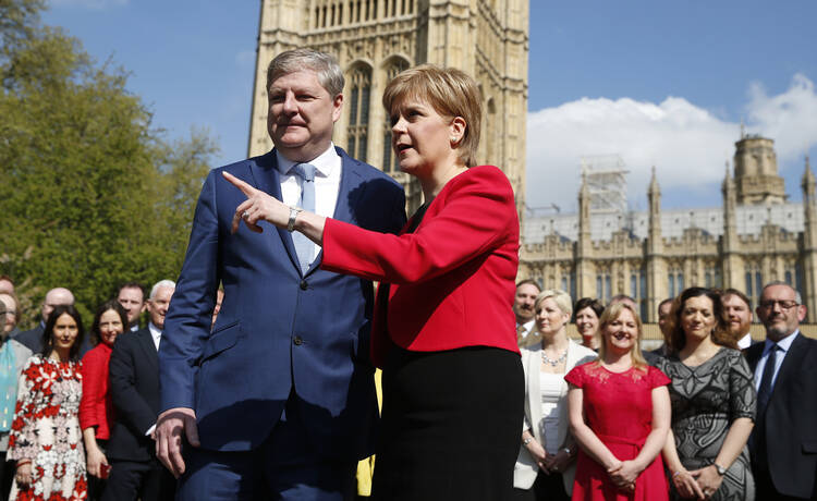 Scotland's First Minister Nicola Sturgeon, with lawmaker Angus Robertson an SNP member of the UK Parliament, speak to the media outside the Palace of Westminster in London, Wednesday, April 19, 2017. British Prime Minister Theresa May on Tuesday called for a snap June 8 general election, seeking to strengthen her hand in European Union exit talks and tighten her grip on a fractious Conservative Party. (AP Photo/Alastair Grant)