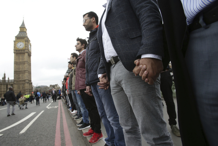 Londoners link hands during a commemorative event to mark last week's attack outside Parliament on Westminster Bridge on March 29. (Yui Mok/PA via AP)
