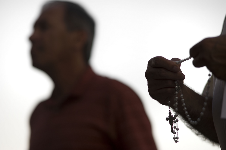 An attendee prays the rosary Oct. 1 during a public session on the issue of clergy sexual abuse at Our Mother of Confidence Parish Hall in San Diego. (CNS photo/David Maung)
