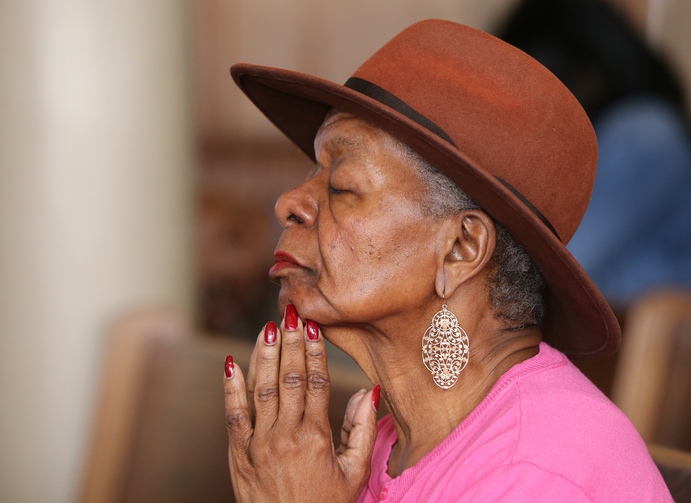 An elderly woman prays during Mass Nov. 13 at St. Peter Claver Church in Baltimore (CNS photo/Bob Roller).