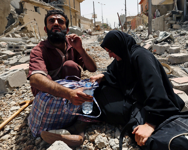 Displaced Iraqis rest amid rubble after fleeing fighting between Iraqi Counter Terrorism Service forces and Islamic State militants May 15 in Mosul. (CNS photo/Danish Siddiqui, Reuters)