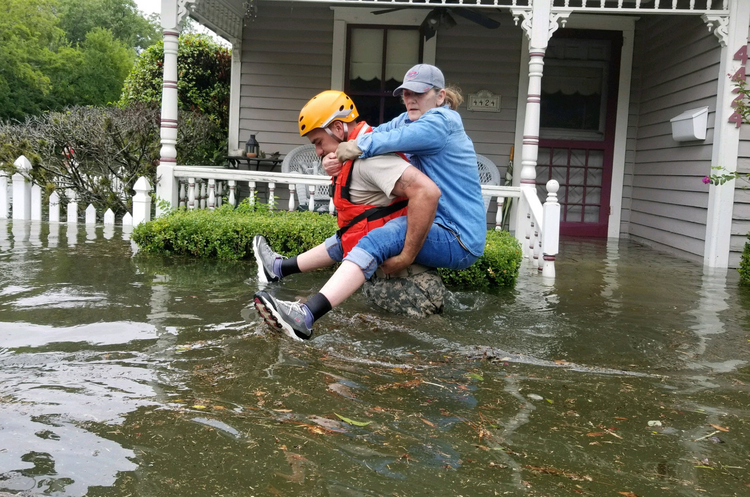A Texas National Guard soldier carries a woman on his back Aug. 27 during rescue operations around Houston, Tex (CNS photo/courtesy Texas Military Department).