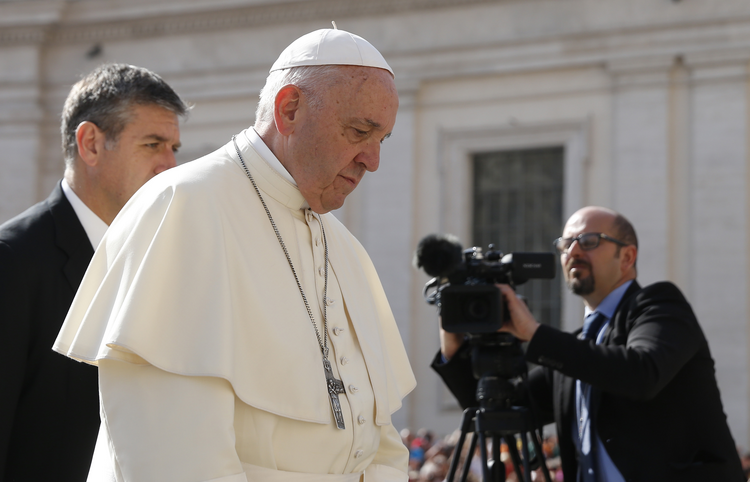 Pope Francis walks past a video journalist during his general audience in St. Peter's Square at the Vatican April 25. (CNS photo/Paul Haring)