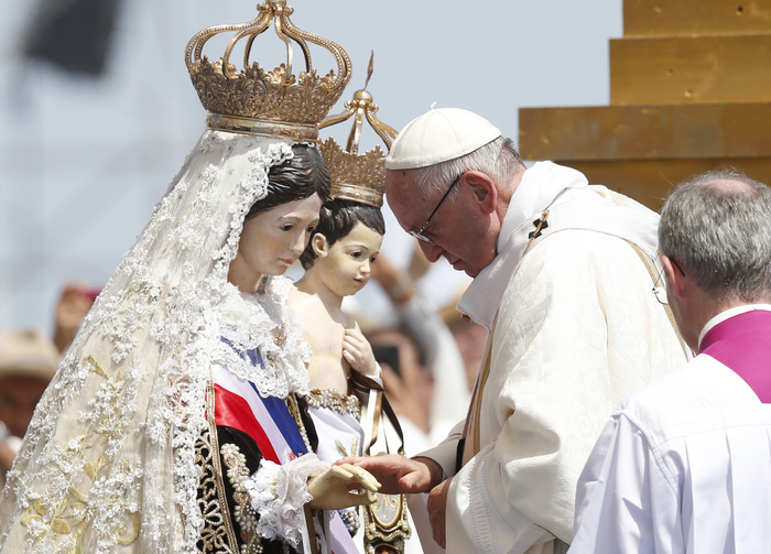 Pope Francis touches a statue of Mary and Jesus after crowning it during Mass at Lobito beach in Iquique, Chile, Jan. 18. (CNS photo/Paul Haring)