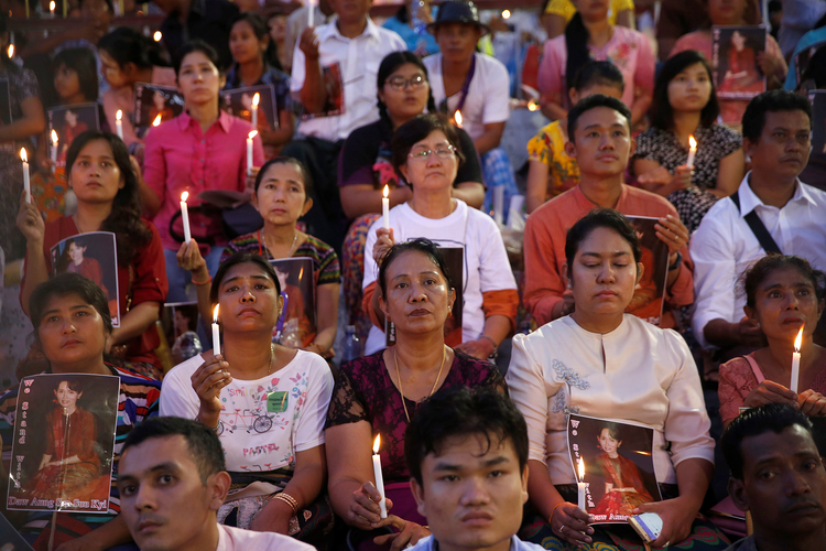 People hold photos of Myanmar state counselor Aung San Suu Kyi during an Oct. 10 candlelight interfaith prayer service in Yangon (CNS photo/Soe Zeya Tun, Reuters).