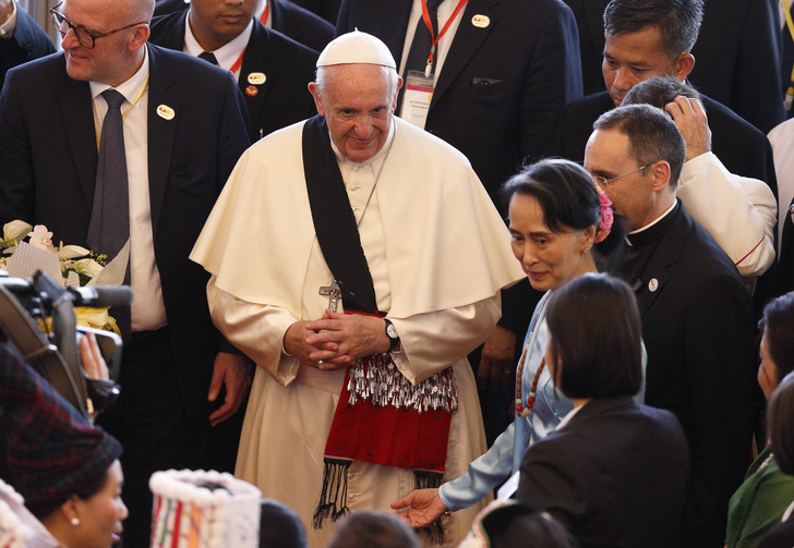 Pope Francis wears a gift as he arrives with Aung San Suu Kyi, state counselor and foreign minister of Myanmar, for a meeting with government authorities, members of civil society and the diplomatic corps at the Myanmar International Convention Center in Naypyitaw, Myanmar, Nov. 28. (CNS photo/Paul Haring)