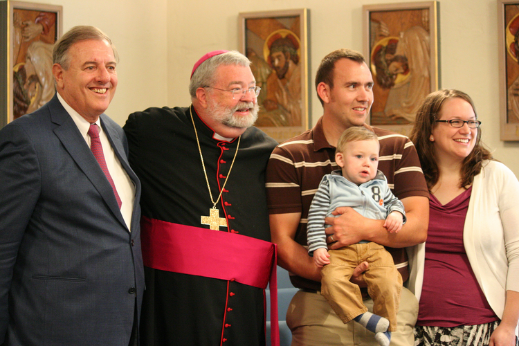 James Fulton Engstrom is held by his parents, Travis and Bonnie Engstrom, Sept. 7, 2011, at the Spalding Pastoral Center in Peoria, Ill., as a tribunal began investigating the boy's miraculous healing through the intercession of Archbishop Fulton J. Sheen. With them are Andrea Ambrosi, postulator of Archbishop Sheen's sainthood cause, and Peoria Bishop Daniel R. Jenky. (CNS photo/Jennifer Willems, The Catholic Post)