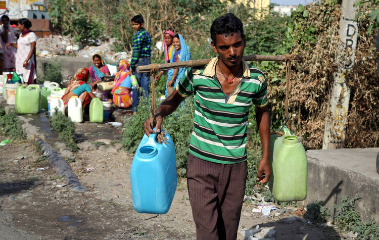 A man carries containers filled with drinking water after taking it from a public tap at a roadside in Jammu, India, May 23, 2016 (CNS photo/Jaipal Singh, EPA).