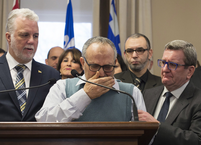Mohamed Labidi, the vice-president of the mosque where an attack happened, is comforted by Quebec Premier Philippe Couillard, left, and Quebec City mayor Regis Labeaume, right, during a news conference on Jan. 30 about the fatal shooting at the Quebec Islamic Cultural Centre on Sunday. (Jacques Boissinot/The Canadian Press via AP)