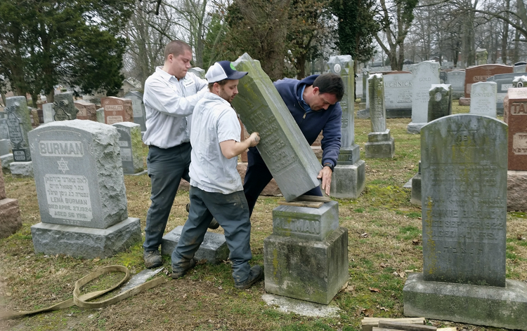 Rosenbloom Monument Co. workers from left, Nathan Fohne, Derek Doolin and Philip Weiss hoist a headstone at the Chesed Shel Emeth Cemetery in University City, Mo., where over 150 headstones were tipped over. (AP Photo/Jim Salter)