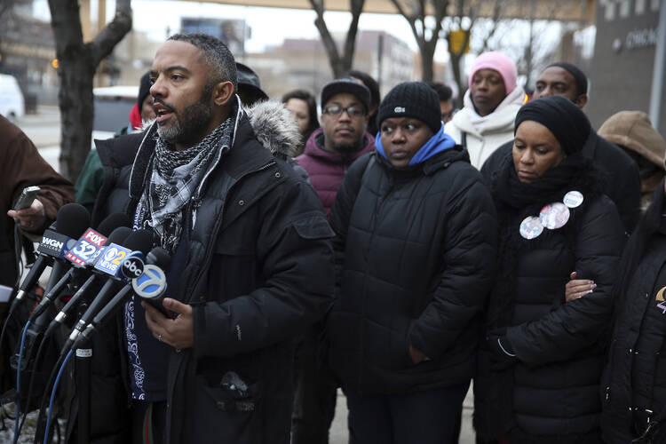 Kofi Ademola, left, of the group Black Lives Matter Chicago, and other protesters talk to the media outside the Chicago Police District 1 headquarters on South State Street in Chicago on Jan. 13. Speakers said Chicagoans already knew from experience what the Department of Justice said in its report critical of the Chicago Police department. (Terrence Antonio James/Chicago Tribune via AP)
