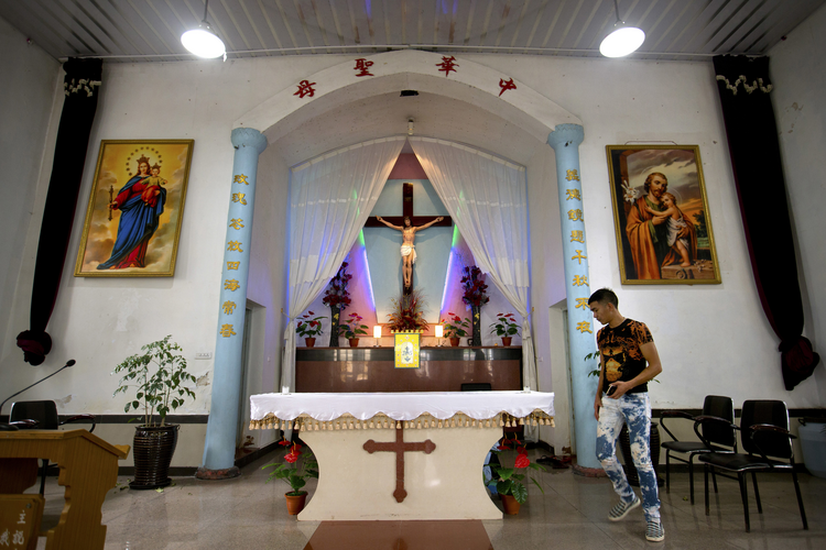 In this July 30, 2015, file photo, a parishioner walks past the altar as members of Lower Dafei Catholic Church hold an impromptu prayer vigil as they wait for Chinese officials to arrive and cut down their church's cross in Lower Dafei Village near Wenzhou in eastern China's Zhejiang Province. (AP Photo/Mark Schiefelbein, File)