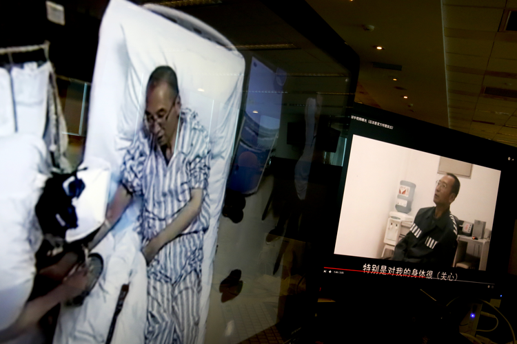 Video clips show China's jailed Nobel Peace laureate Liu Xiaobo lying on a bed receiving medical treatment at a hospital, left, and Liu saying wardens take good care of him, on a computer screens in Beijing on June 29. (AP Photo/Andy Wong)