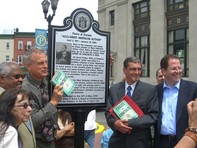 The dedication ceremony of Pietro di Donato, Plaza in Union City, New Jersey, May 22, 2010. Holding up a copy of di Donato's novel, Christ in Concrete, is the author's son, Richard (Wikicommons/Luigi Novi).