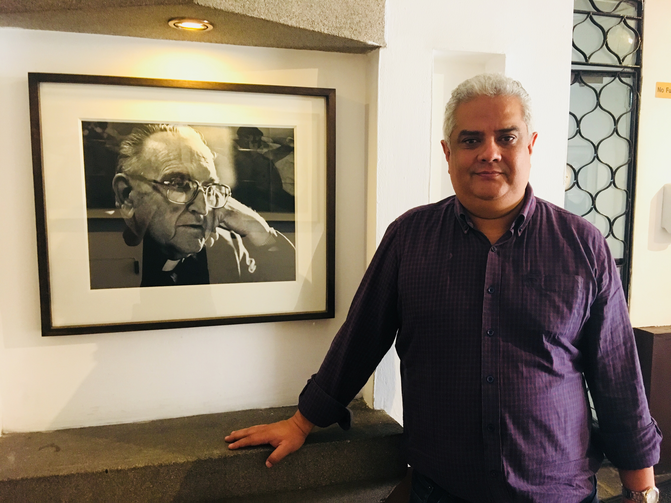 Nery Rodenas, director of the Human Rights Office of the Archdiocese of Guatemala, stands beside a portrait of Bishop Juan José Gerardi. (Jackie McVicar)
