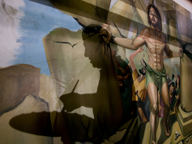 In this Monday, April 24, 2017 photo, the shadow of Coptic Christian Ayman William is reflected on a dome where he is painting a biblical scene of Samson, at Mar Girgis Church in Zawiya al-Hamra, in Cairo, Egypt. (AP Photo/Amr Nabil)