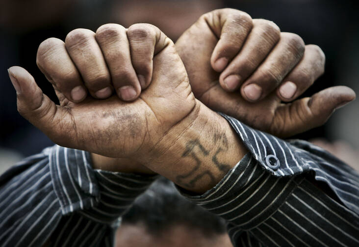 In this Friday, April 14, 2006 file photo, Egyptian Copts cross their wrists in defiance outside the Saints Church in the Sidi Bishr district of Alexandria in Egypt. Egypt's Coptic Christians have become the preferred target of Islamic State radicals operating in the Arab world's most populous nation, seeking to sow discord, undermine President Abdel-Fattah el-Sissi, and split the country. (AP Photo/Ben Curtis, File)
